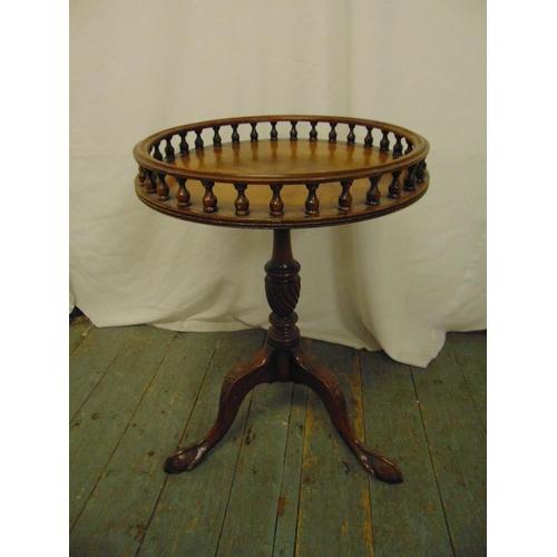 19 - A circular mahogany side table with raised pierced gallery on three scroll legs...