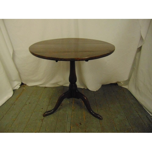20 - A Georgian mahogany tilt top circular occasional table on three outswept legs...