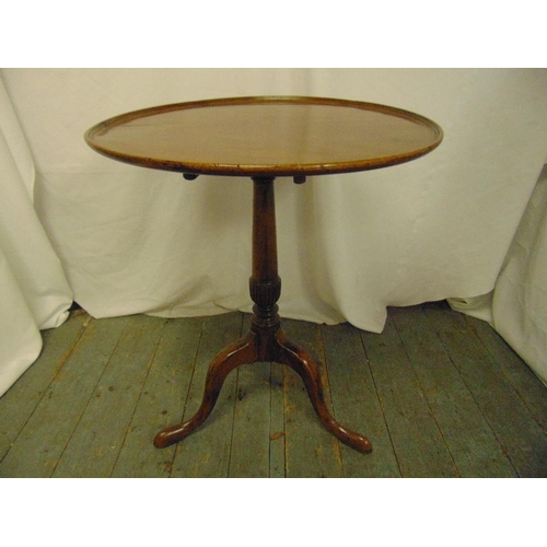 21 - A Victorian mahogany circular tilt top occasional table on three outswept legs...