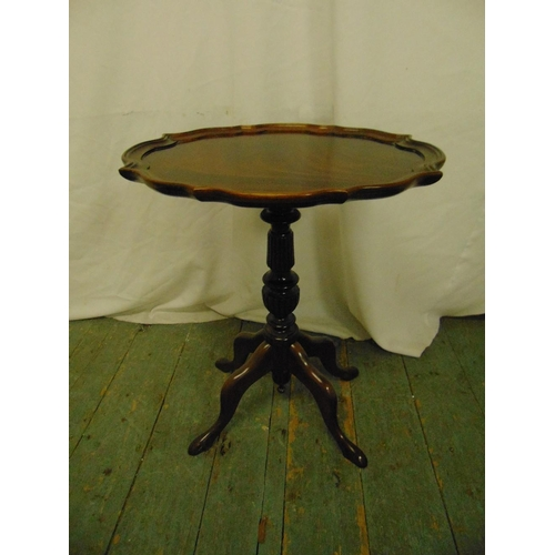 22 - A mahogany wine table with moulded border, baluster stem and four scroll legs...