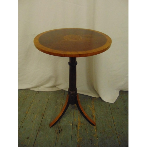 23 - An Edwardian mahogany circular side table on three outswept legs...