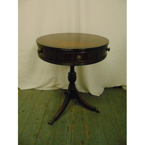 24 - A mahogany circular drum top table with two drawers on three outswept legs with brass castors...
