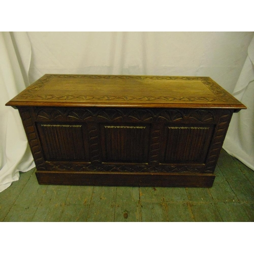26 - A 19th century rectangular oak chest with carved sides and hinged cover...
