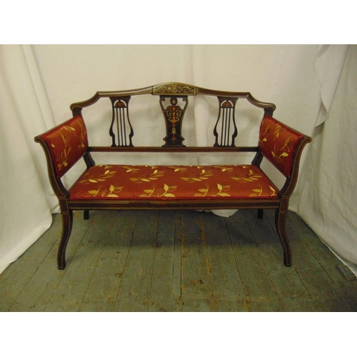 29 - An Edwardian two seater settle with upholstered seat and arms, pierced slat inlaid back on four scro...