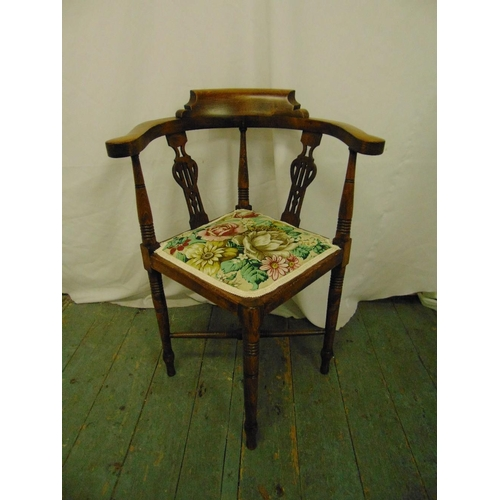 32 - A Victorian oak corner chair with pierced slats, upholstered seat and four turned cylindrical legs...