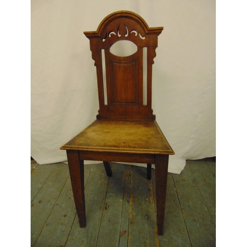 34 - A 19th century mahogany hall chair with pierced architectural back on four tapering rectangular legs...