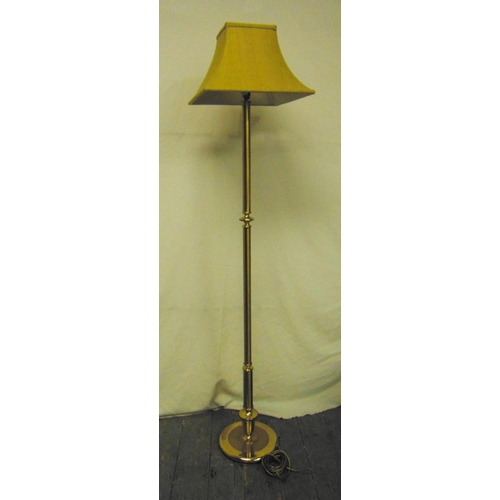 38 - A brass standard lamp of cylindrical form on raised circular base with silk shade...