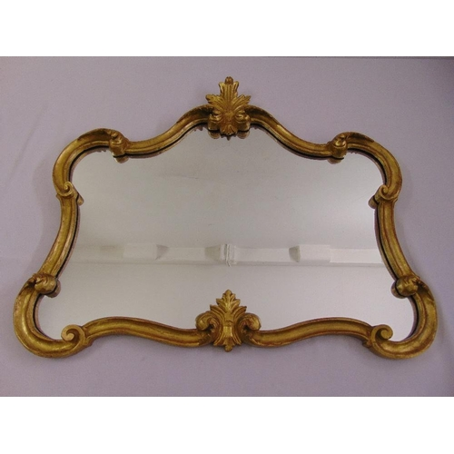 42 - A shaped rectangular gilded wooden wall mirror with shell and leaf motifs...