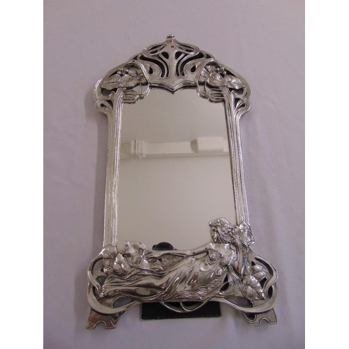 44 - A silvered Art Nouveau style table mirror shaped rectangular with stylised vegetation and a classica...