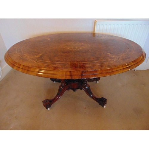 10 - A Victorian oval inlaid walnut tilt top hall table on four outswept legs with original casters...