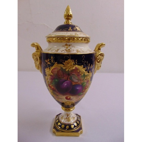 113 - A Coalport vase and cover with gilded rams mask side handles the sides painted with fruits, the dome...