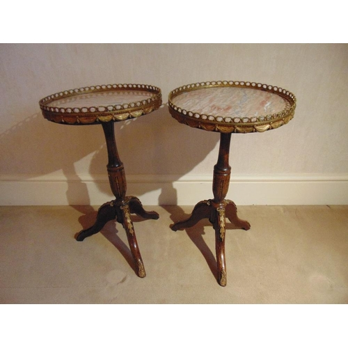 13 - A pair of circular gilded metal and marble side tables on three outswept legs...