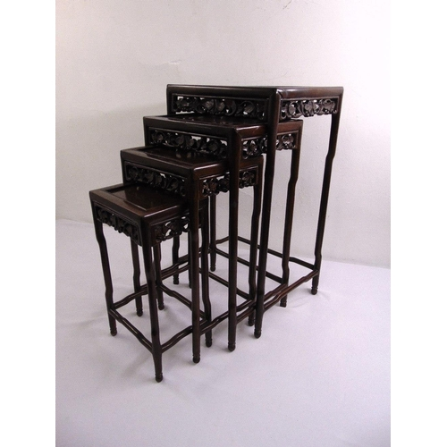 16 - A 20th century quartetto of Chinese hardwood nesting tables, each of rectangular form with foliate c...