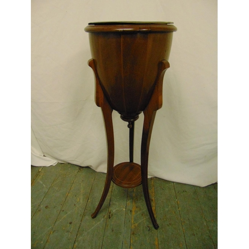 20 - An Edwardian mahogany plant stand of conical form on triform base...