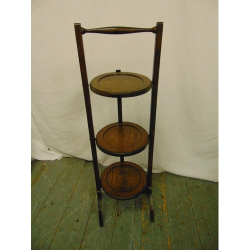21 - An oak three tier plate stand of customary form...