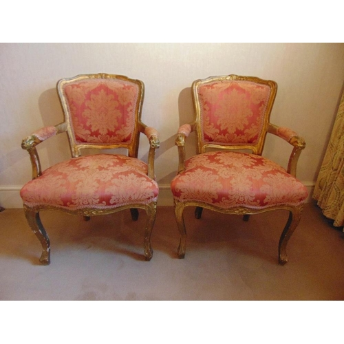 26 - A pair of French upholstered bedroom armchairs on cabriole legs...