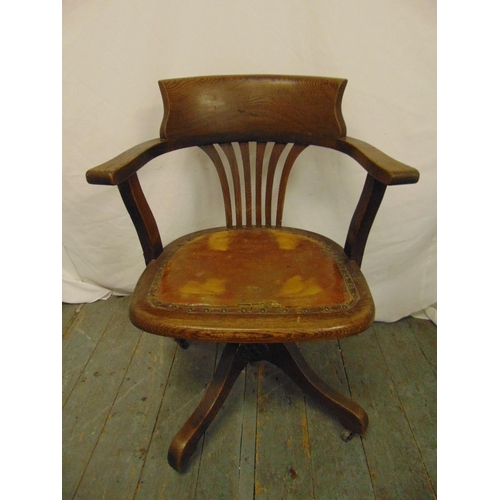 28 - An early 20th century oak captains chair with leather seat and original castors, label to base A M C...