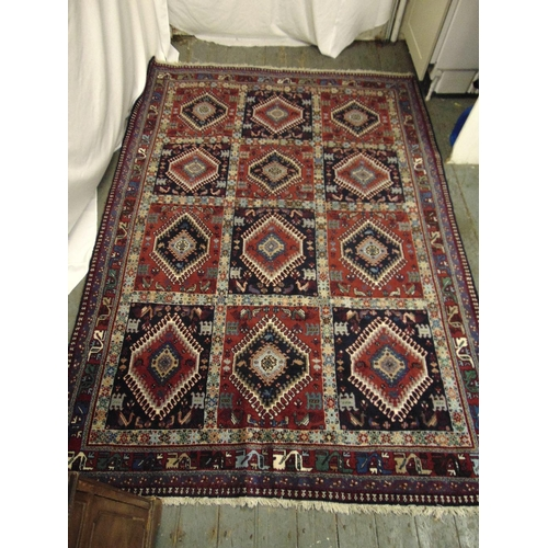 32 - A Persian Yalameh carpet, predominately brown, red and blue, formed as rows of diamond medallions wi...