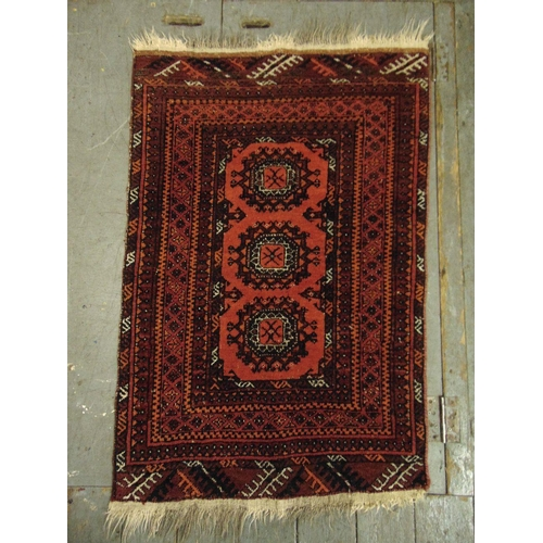 33 - Persian wool carpet red and orange ground with repeating geometric pattern and border, 107 x 73cm...
