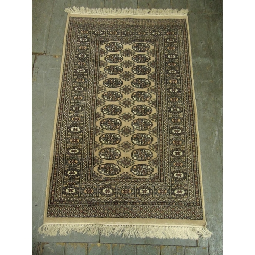 37 - A Persian wool carpet tan ground with repeating geometric pattern and border, 150 x 95cm...