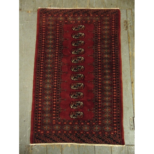 38 - A Persian wool carpet red ground with repeating geometric pattern and border, 121 x 79cm...
