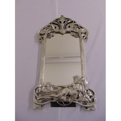 41 - A silvered Art Nouveau style table mirror shaped rectangular with stylised vegetation and a classica...