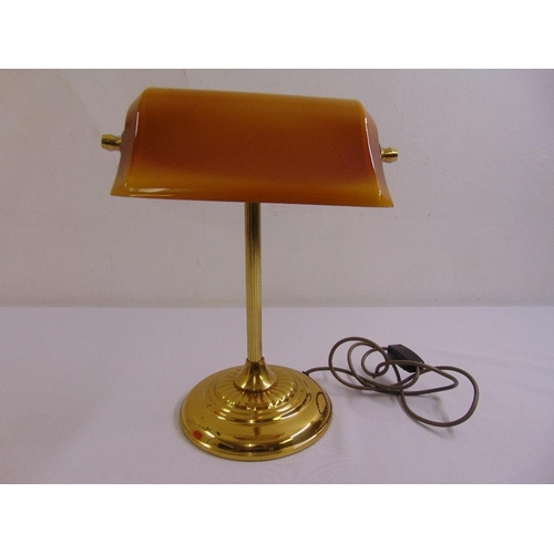 46 - A brass desk lamp on raised circular base with integrated glass shade...