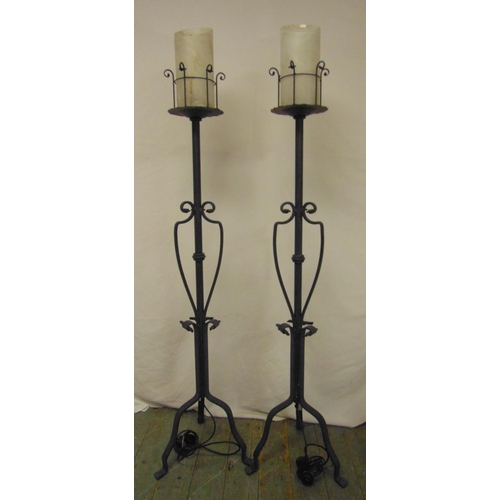 49 - A pair of painted wrought iron candle holders converted to electricity on three scroll supports...