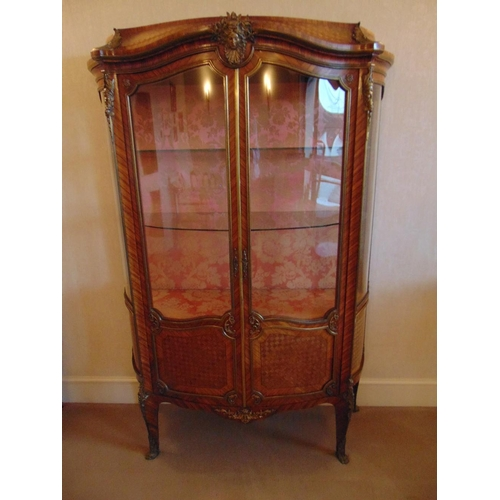 7 - A French style two door glazed Kingswood display cabinet with applied gilded metal mounts...