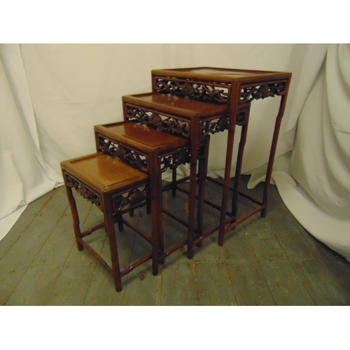11 - A 20th century quartetto of Chinese hardwood nesting tables of rectangular form with foliate carved ...