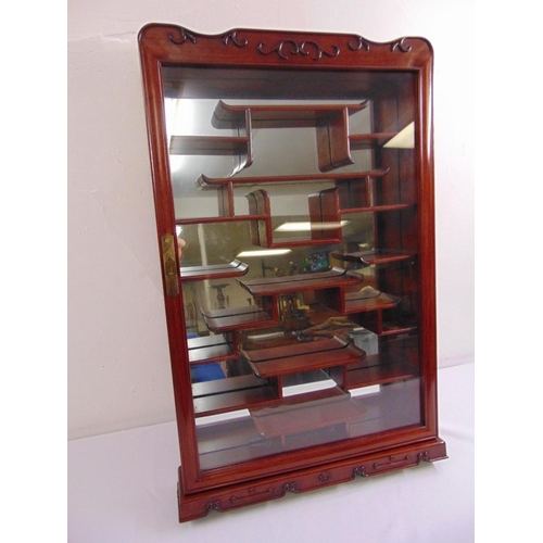 12 - A wall mounted Oriental style miniatures display cabinet with mirrored back...