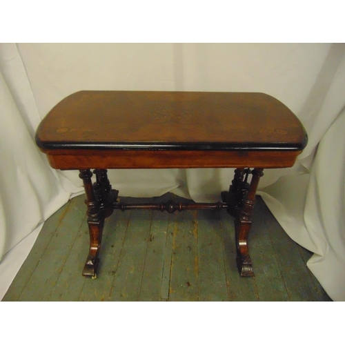 13 - A Victorian mahogany rectangular games table, hinged top on scrolling supports...