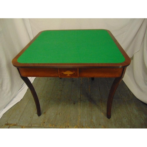14 - A rectangular mahogany games table with hinged top revealing a green baize on four sabre legs...