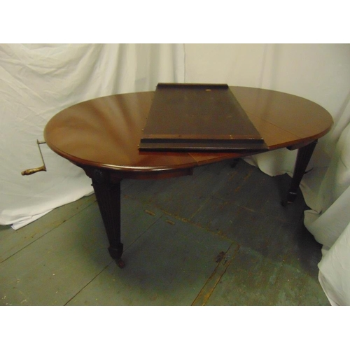 16 - A Victorian shaped oval mahogany dining table with two drop in leaves and Joseph screw mechanism, by...