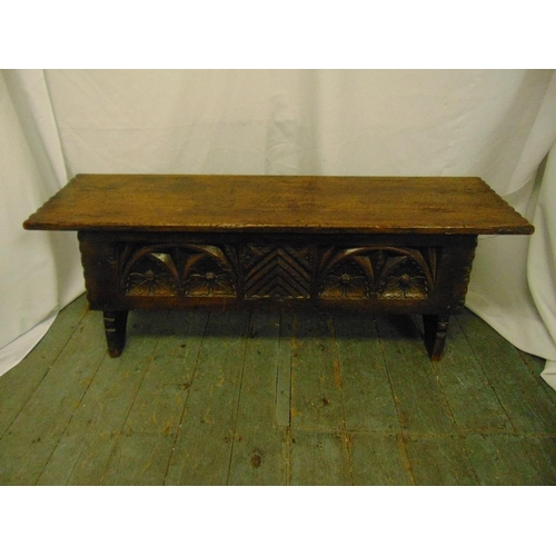 18 - A rectangular oak monks bench with carved sides, hinged cover on four turned legs...