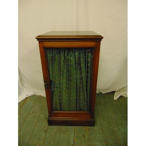 19 - A Regency rectangular mahogany cabinet with hinged glazed door on rectangular plinth...