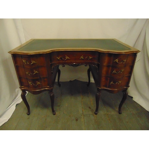2 - An Edwardian shaped rectangular mahogany kneehole desk with tooled leather top, brass handles, on ca...