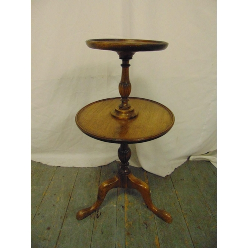 20 - A mahogany circular two tier tea table on three outswept legs...