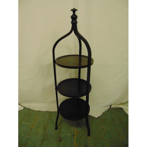 23 - A three tier mahogany tea stand surmounted by baluster finial on three scrolling legs...