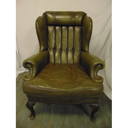 27 - A green leather armchair, button back on scroll legs...