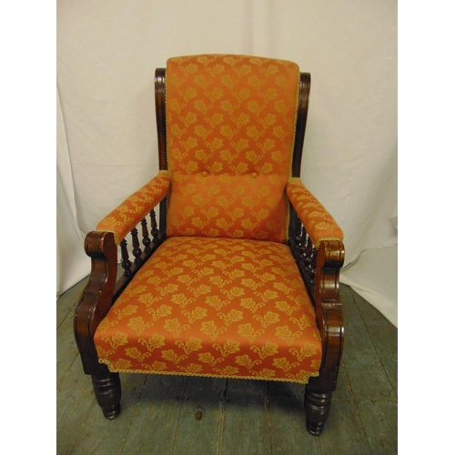 28 - A Victorian mahogany upholstered armchair with galleried arms on turned cylindrical legs...