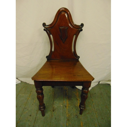 36 - A Victorian mahogany hall chair, pierced back on turned baluster legs...