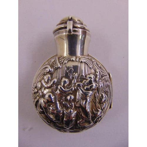 389 - A glass scent bottle with drop stopper in hinged silver case chased with figures and with hinged dom...