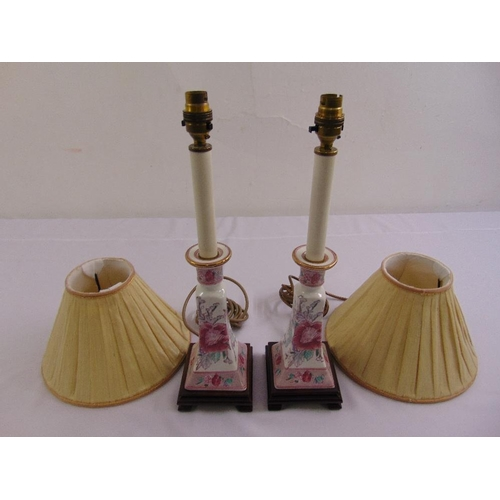 43 - A pair of porcelain table lamp stands decorated with floral sprays and with shades...