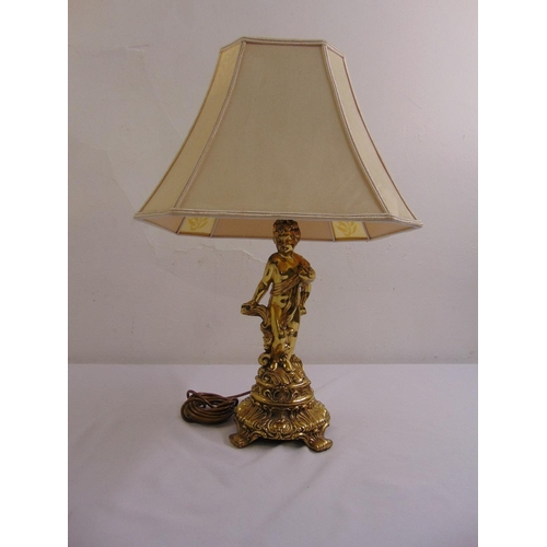 48 - A gilded metal table lamp in the form of a putti on raised circular base with silk shade...