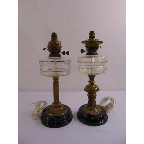 51 - A pair of late 19th century metal oil lamps with glass reservoirs converted to electricity...