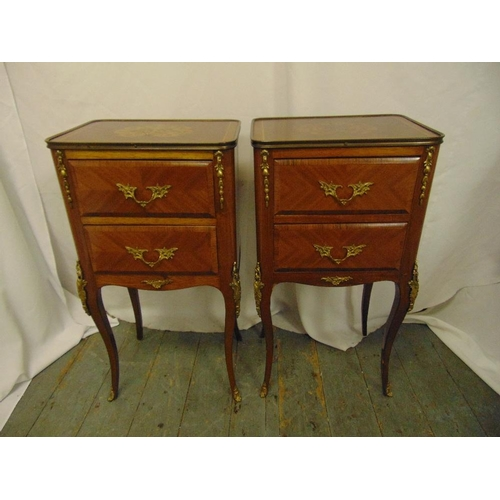 7 - A pair of rectangular two drawer side tables with applied gilded metal mounts on four cabriole legs...