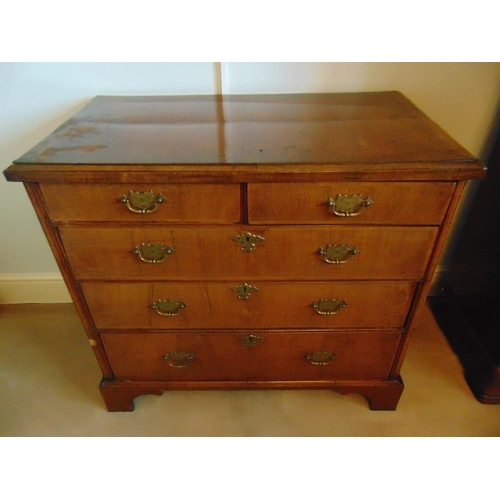 11 - A rectangular mahogany chest of drawers with brass swing handles, on four bracket feet...
