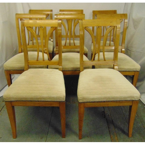 29 - A set of eight Biedermeier style fruitwood dining chairs with upholstered seats on sabre legs...
