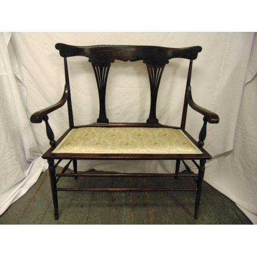 33 - A Victorian mahogany two seater settle with scrolling arms, pierced slats on four tapering cylindric...